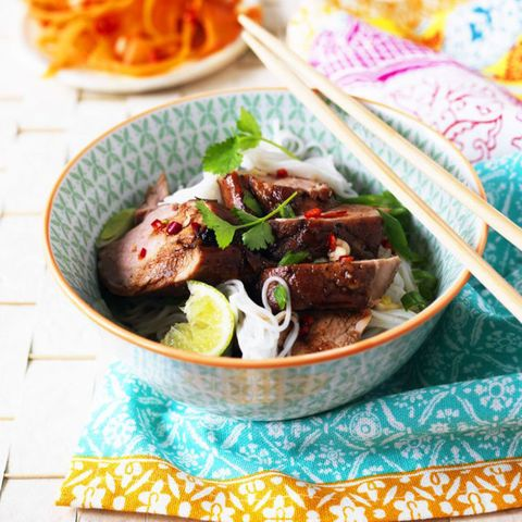 Pork and noodles in a bowl with chopsticks