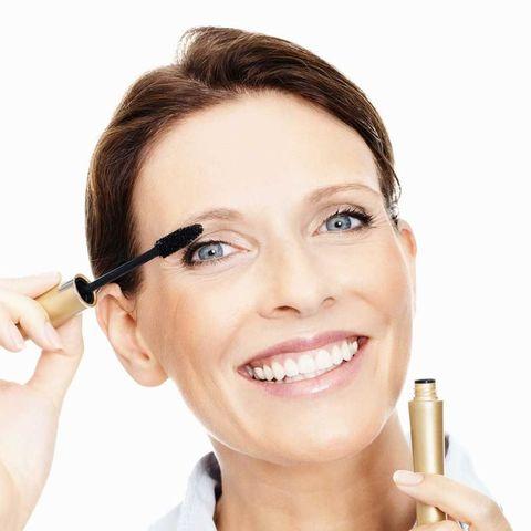 Mature woman applying make up