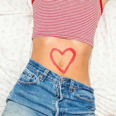 Woman with heart on thin stomach