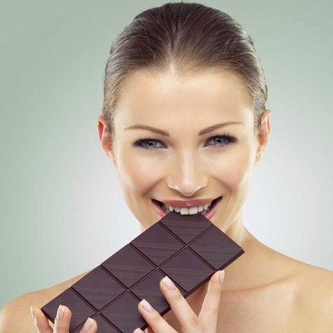 Beautiful woman eating bar of chocolate