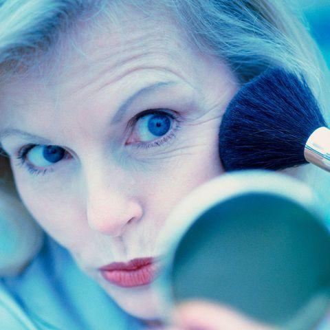 gettymar15 older woman applying blusher1000sq