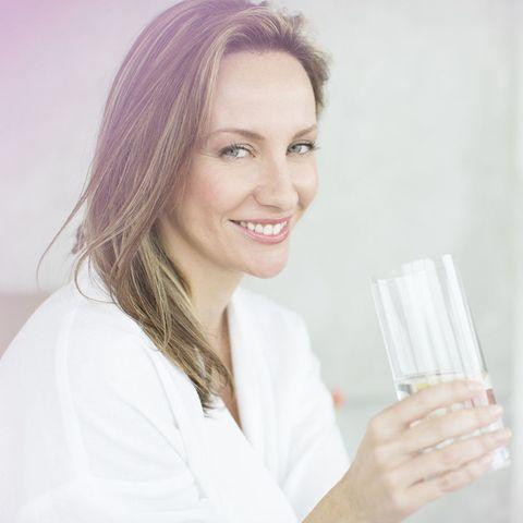 Woman having glass of water in bedroom