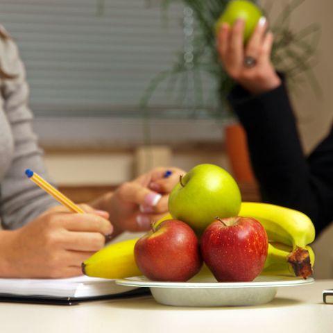 Fruit on desk, two women in background