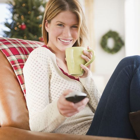 Woman watching TV and drinking hot drink