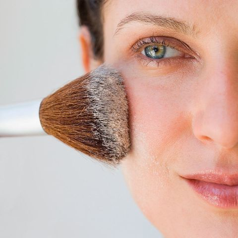 Woman applying loose powder to face