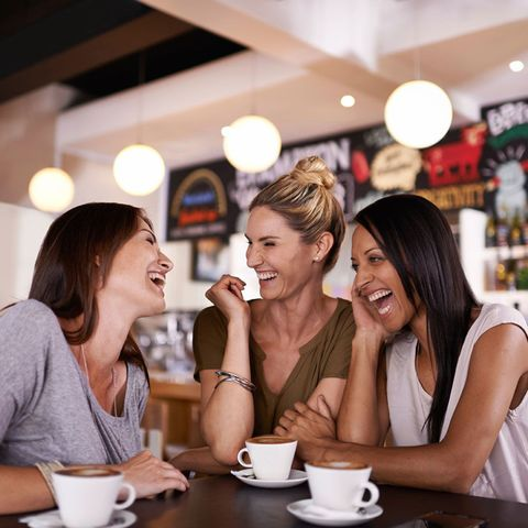 Friends laughing together in a cafe