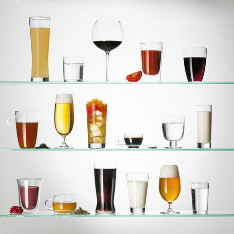 A collection of various types of drinking glasses filled with a variety of beverages