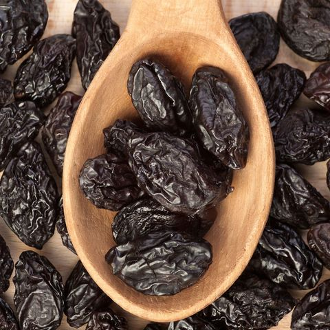 Prunes in wooden spoon
