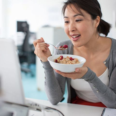 Woman eating cereal at desk