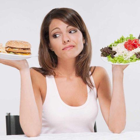 Woman choosing between a burger and a salad