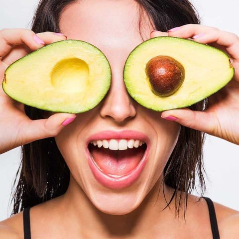 Woman holding avocados in front of her eyes