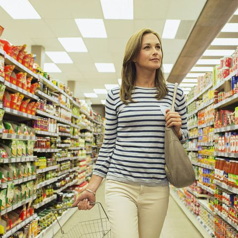 Woman with shopping basket in grocery store
