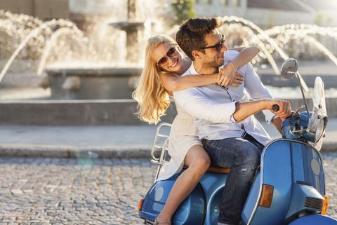 Happy couple on a vespa in Italy
