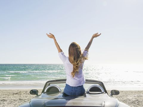Happy woman sitting on a convertible car at the beach