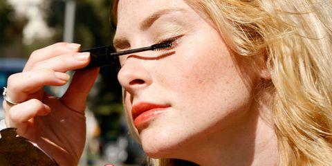 Woman applying waterproof mascara