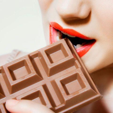 Woman eating bar of chocolate