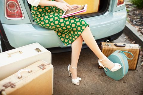 Woman sitting in car boot with luggage