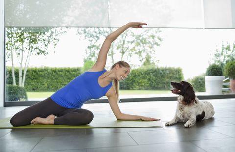 Woman doing yoga with dog