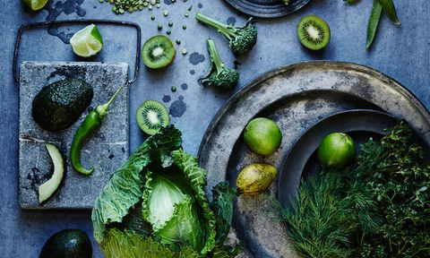 Green vegetables and fruit on a dark surface