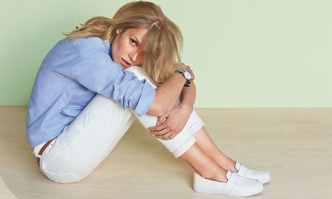 Model wearing white jeans and blue shirt