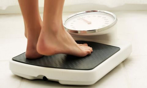 Woman's feet stepping onto bathroom scales