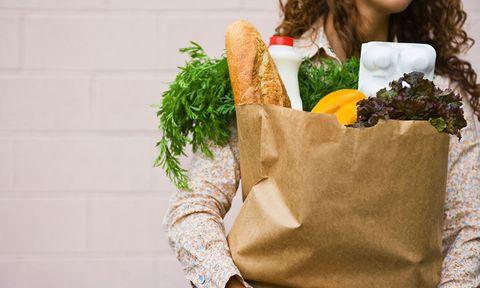woman carrying brown bag full of vegetables