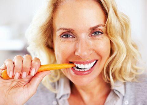 Mature woman eating carrot