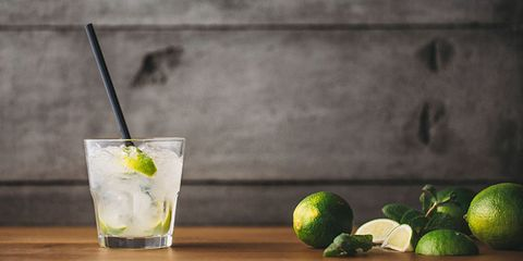 Clear drink in a glass with limes
