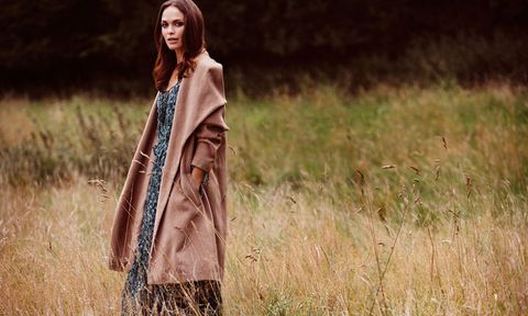 Woman wearing a winter coat and maxi dress in a field