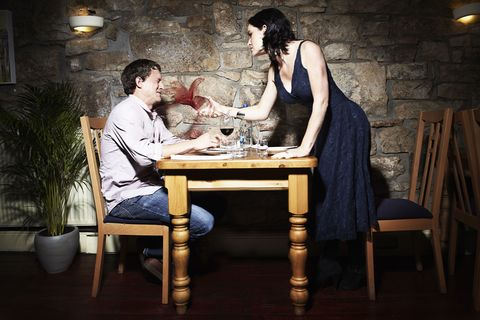 Woman throwing wine on a man during a date