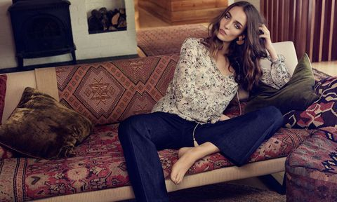 Woman in jeans on a patterned sofa