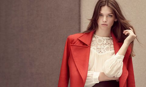 Brunette woman in red coat and white blouse