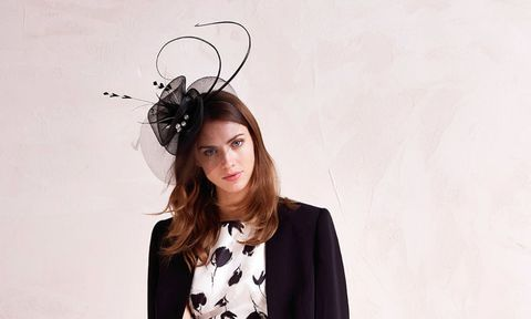 Brunette woman in a fascinator and monochrome dress