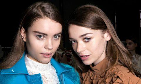 Two brunette models backstage at fashion week