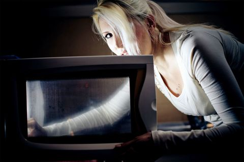 Woman reheating food in a microwave