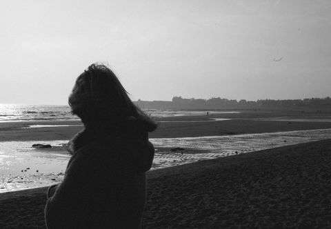 Woman stares out to sea