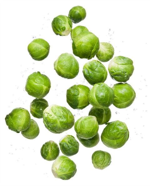 Healthy eating clean organic fresh vegetable brussel sprouts flying and bouncing up into the air in studio on a white background for wellness