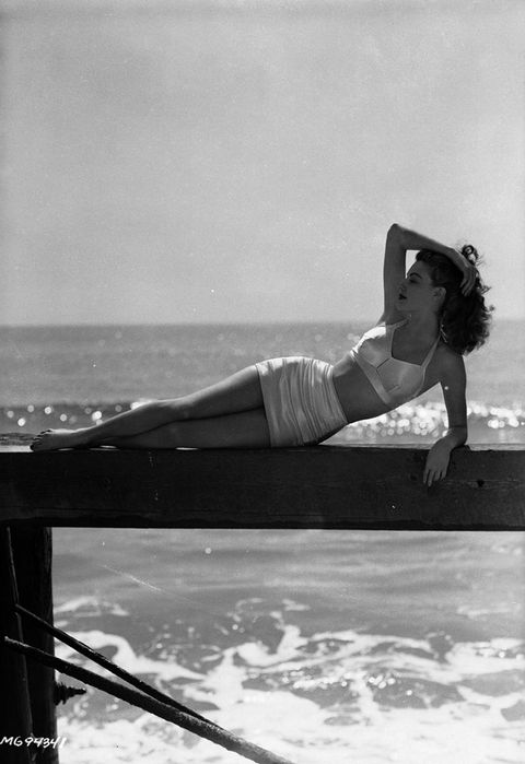 25th March 1943:  Actress Ava Gardner (1922 - 1990) lounges on a wooden jetty on the beach, wearing an elegant bikini.  (Photo by Eric Carpenter/John Kobal Foundation/Getty Images)