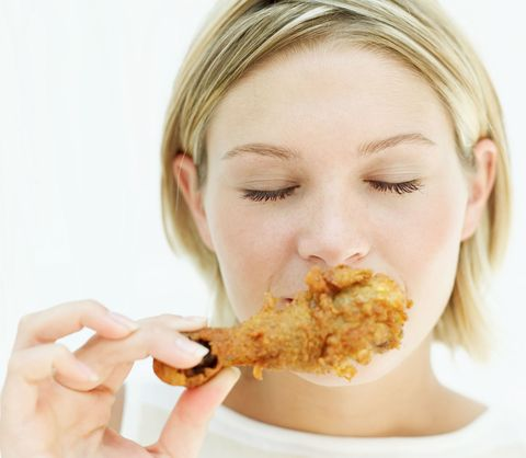 Woman eating fried chicken