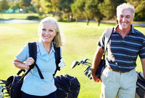 Middle aged couple playing golf