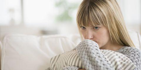 Worried woman sat on sofa