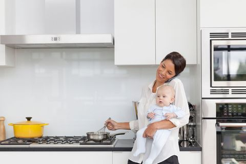 Busy mum cooks, looks after child and takes phone call.