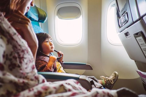 mother and child on plane, watching inflight entertainment