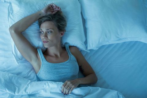 Woman lays in bed, thinking