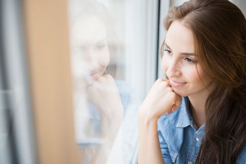 Woman looking out of window absentmindedly