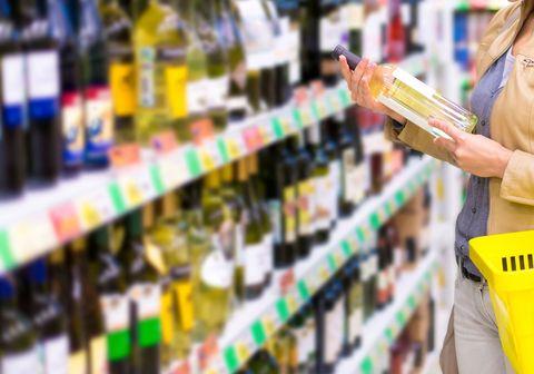 Woman buying wine at supermarket