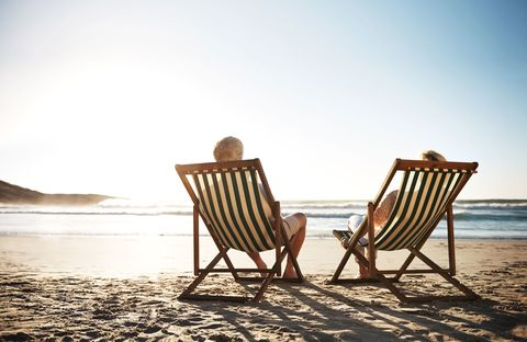 Older couple relax in deck chairs on a beach as the sun sets