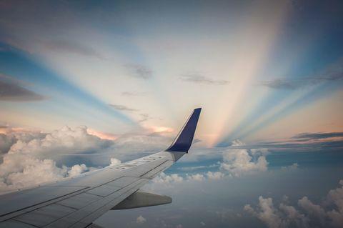 Plane flies through clouds as sun sets