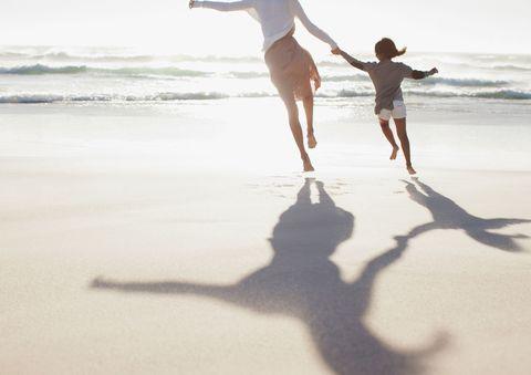 Mum and daughter running on beach