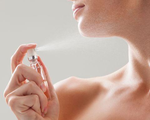 Woman spraying perfume